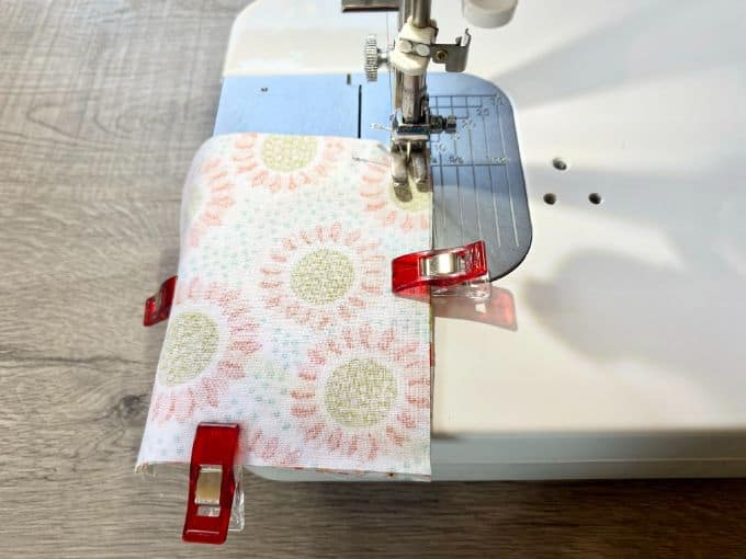 Sewing machine sewing around perimeter of fabric squares sandwiched together