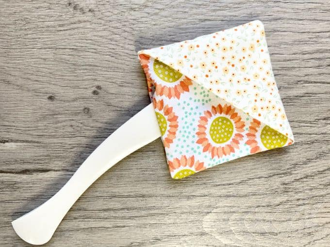 Turning tool inside square fabric opening of corner bookmark