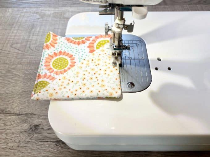 Sewing machine top stitching around fabric corner bookmark with flowers