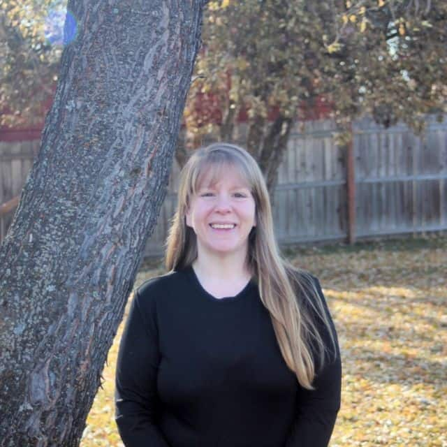 A photo of Kathie Lapcevic standing next to a tree.