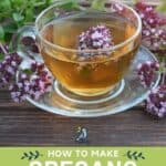 A glass cup full of tea with oregano flowers inside the cup and surrounding the cup with text overaly reading how to make oregano tea.