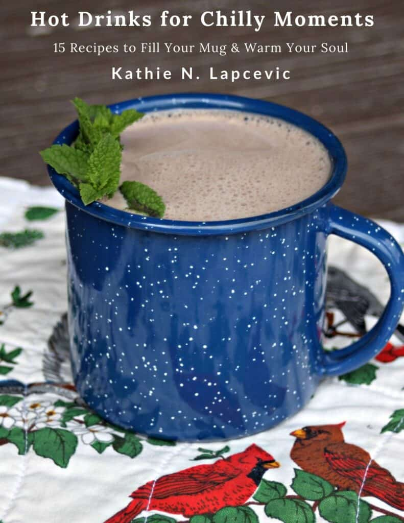 A blue tin cup full of hot cocoa with a sprig of fresh mint sitting on a placemat with cardinals and greenery. Text overlay stating: Hot Drinks for Chilly Moments - 15 recipes to fill your mug and warm your soul by Kathie N. Lapcevic