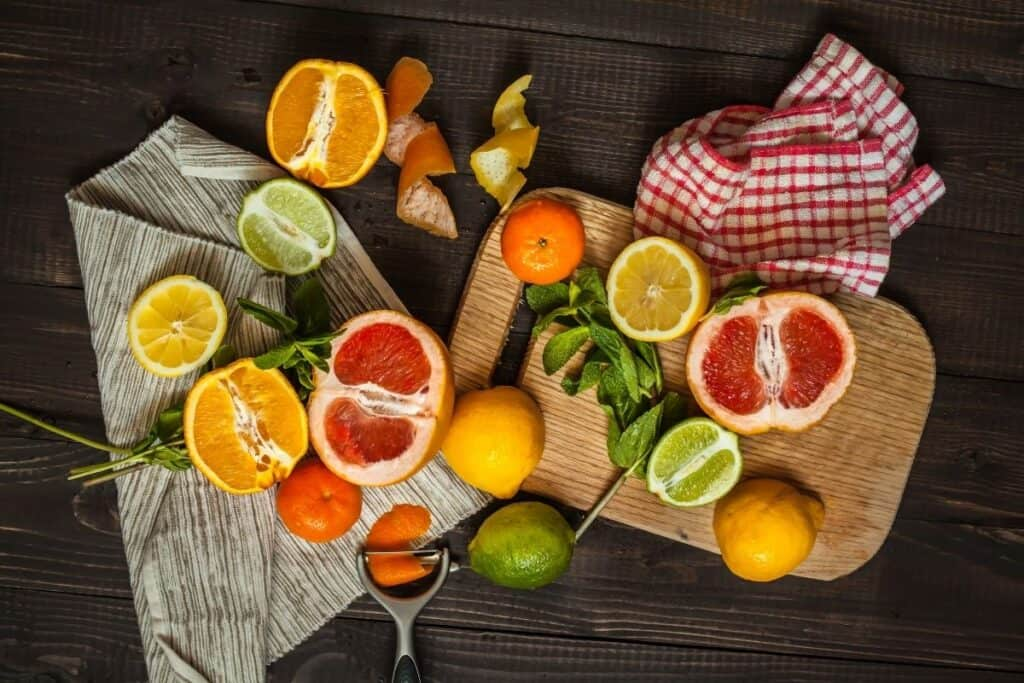 A variety of citrus whole and cut in half on a wooden board and linens scattered on a table.