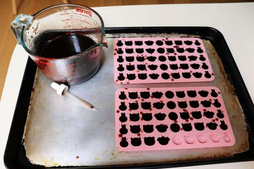 A cookie with 2 pink silicone molds being filled with elderberry syrup gelatin. Sitting next to the molds on the tray is a large glass measuring cup holding more of the liquid gelatin and a small dropper next to it.