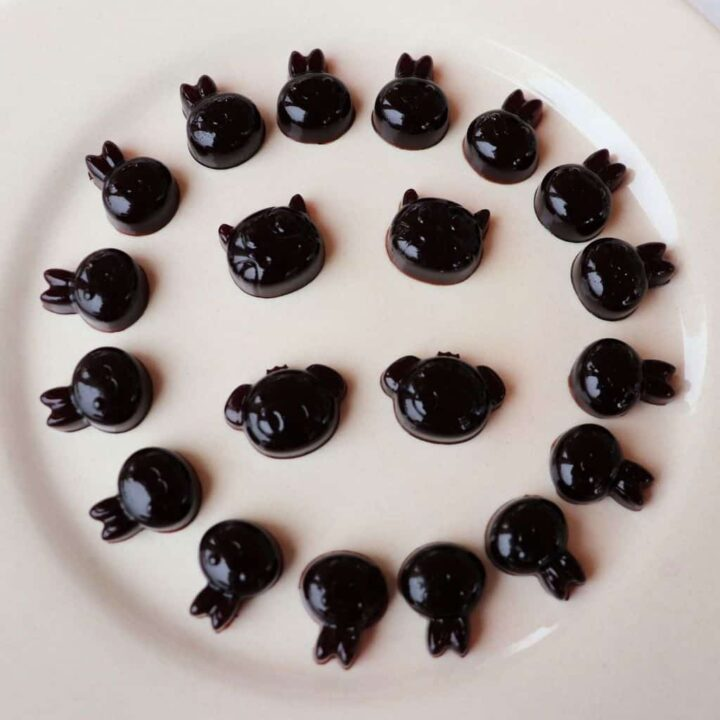A white plate with elderberry syrup gummies in animal shapes around the edge and in the center of the plate.