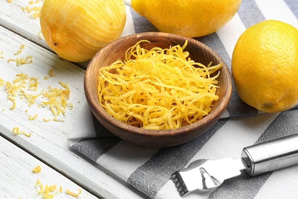 A wooden bowl full of strips of lemon zest surrounded by fresh lemons and steel lemon peeler.