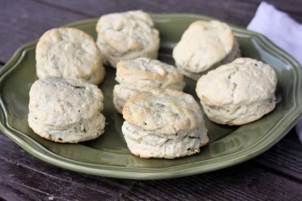 Chive biscuits spread onto a green platter.