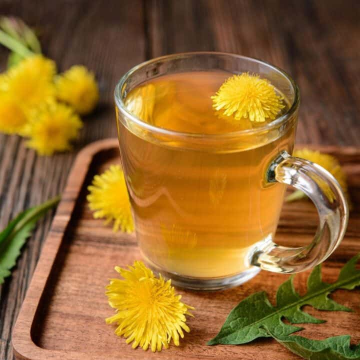 A clear glass mug full of tea with a dandelion blossom floating inside. The mug is sitting on a board surrounded by dandelion flowers and leaves.
