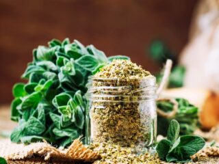 An overflowing jar of dried oregano sitting on a piece of burlap with fresh oregano in the background.