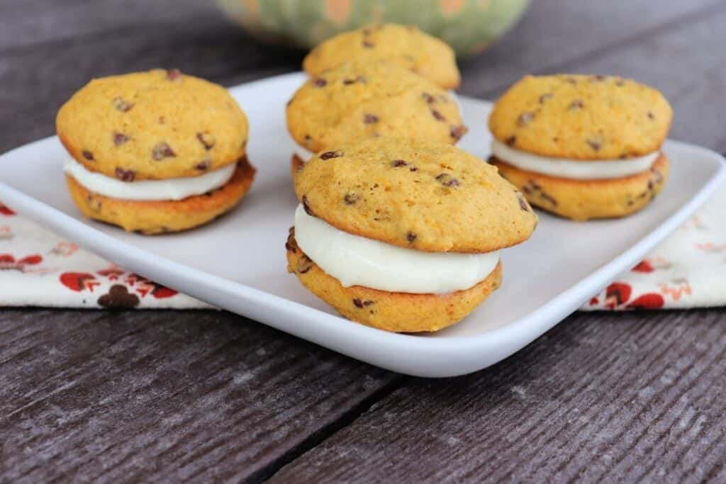A plate full of sandwich cookies with chocolate chips sitting on top of a napkin with a bit of a pumpkin in the background.
