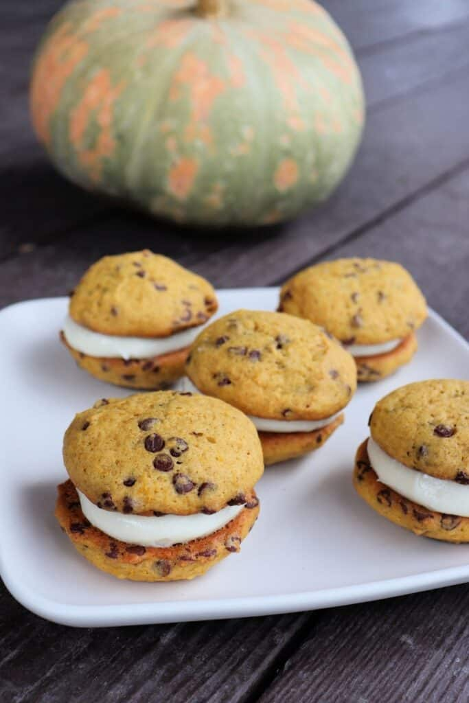 A plate full of sandwich cookies with chocolate chips on a table with a pumpkin in the background.