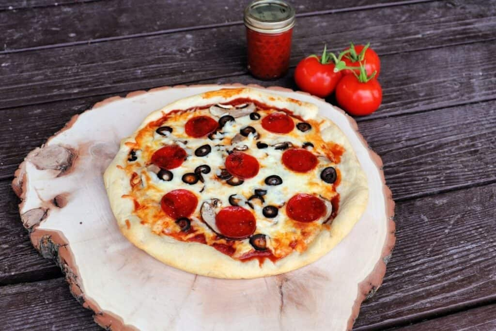 A cooked pizza sitting on top of a round wooden cutting board with fresh tomatoes and a jar of pizza sauce sitting behind it.