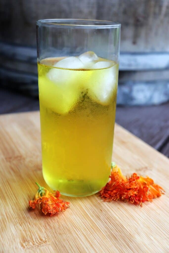 A glass full of honeysuckle tea over ice sitting on a board surrounded by orange honeysuckle blossoms.
