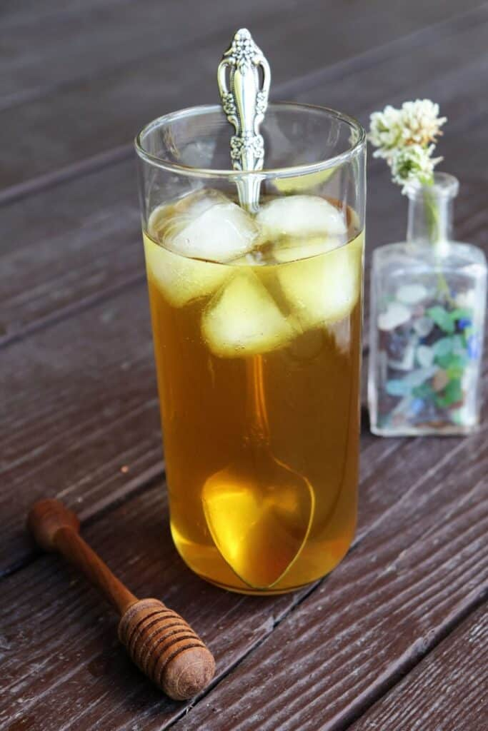 A glass full of ice and white clover tea with a long silver spoon sticking out of it, a wooden honey dipper sitting to the left, a small bottle full of white clovers in the background.