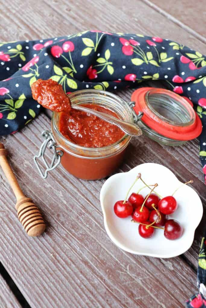 An open jar of sour cherry butter as seen from above with a spoon sitting on top of it, surrounded by fresh cherries in a bowl, a honey dipper, and black cloth with cherries decorating it.