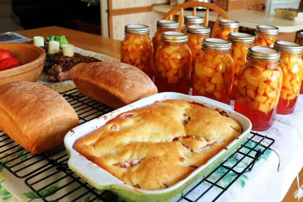 A kitchen table full of quart jars of canned nectarines, 2 loaves of bread on a cooling rack, and a pan of cobbler on a cooling rack.