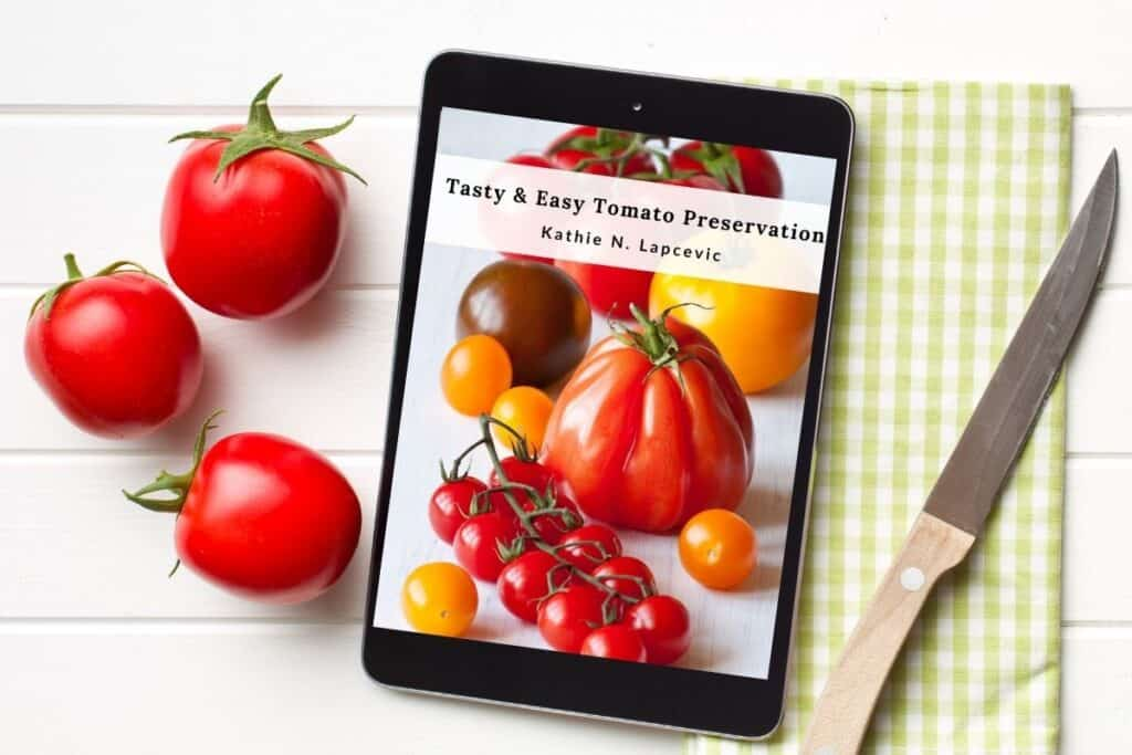 An ereader with the cover of 'Tasty & Easy Tomato Preservation' ebook displayed sitting between fresh tomatoes and a towel with a knife on top.