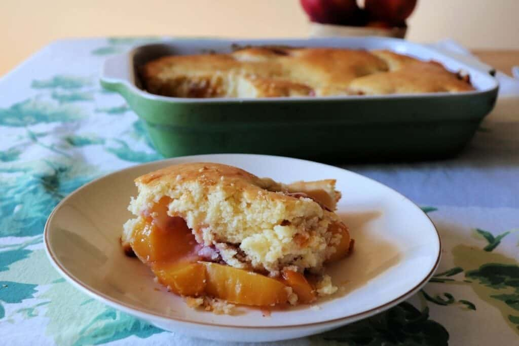 A bowl of nectarine cobbler sitting in front of the rest of the pan.