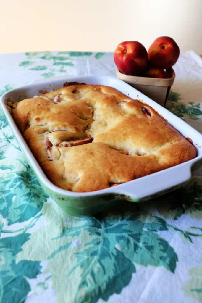 A pan of nectarine cobbler sitting on a table cloth with a basket of fresh peaches in the background.